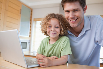 Happy boy and his father using a notebook