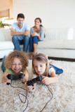 Portrait of children playing video games while their parents are