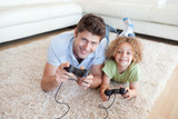 Smiling boy and his father playing video games