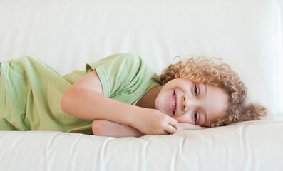Happy boy lying on a sofa