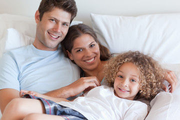 Smiling family relaxing on a bed
