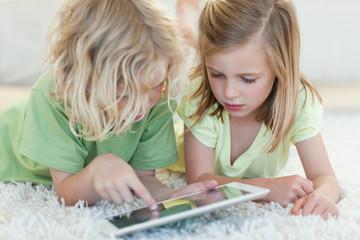 Siblings on the floor using tablet
