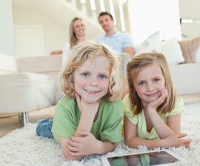 Children on the carpet with tablet and parents behind them