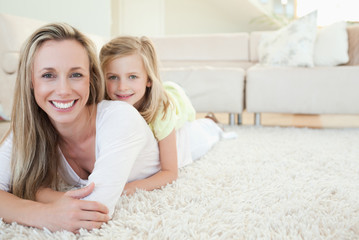 Mother and daughter lying on the floor