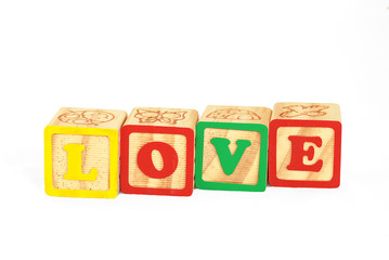 Alphabet blocks over a white surface forming the word love