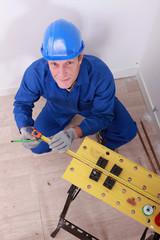 Male plumber using tape measure