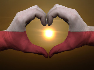 Heart and love gesture by hands colored in poland flag during be