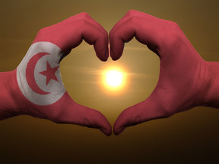 Heart and love gesture by hands colored in tunisia flag during b