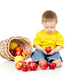 pensive child eating red apples; near basket