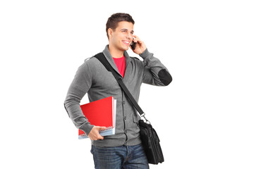 A smiling school boy holding books and talking on a phone