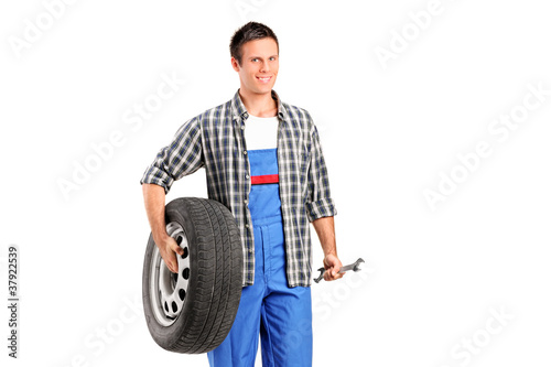 A mechanic holding a spare tire and a wrench