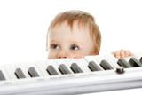 adorable child stanging behind electronic piano