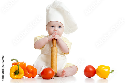 Portrait of a baby wearing a chef hat with healthy  food vegetab