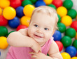 Portrait of a smiling infant playing among colorful balls