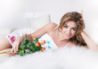 Sexy young girl lying in white bed with fresh roses