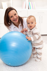 Little baby girl stands by a large exercise ball