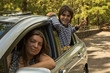 Mom and son traveling together by a car