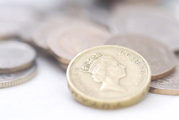 Spilled coins, focus on £1 coin.