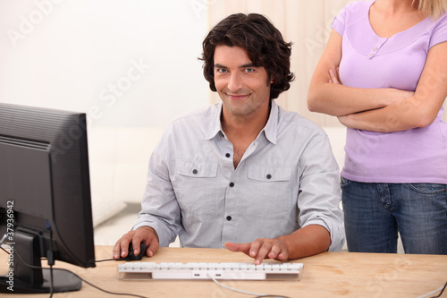 a man doing computer and an angry woman