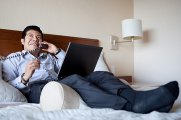 Hispanic businessman using laptop in his hotel room