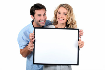 Couple holding white board