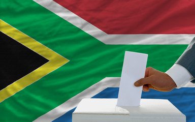 man voting on elections in south africa in front of flag
