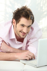 young man lying on couch using laptop