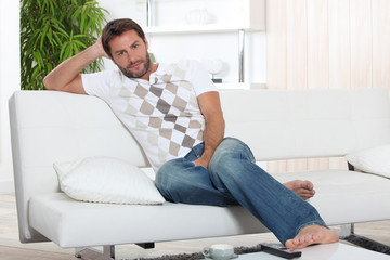 A man resting on his sofa.