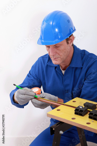 Plumber measuring copper pipe