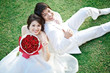 portrait of bride and groom sitting on fresh grass with rose bou