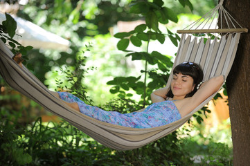 Sleeping young woman in a hammock in a park