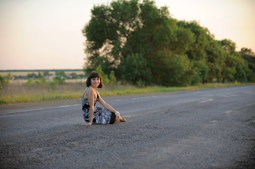 Attractive girl sitting in the middle of a road