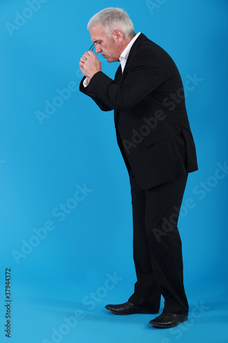 Businessman putting his eyeglasses on to look for an object