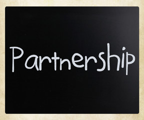 The word 'Partnership' handwritten with white chalk on a blackbo