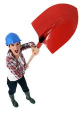 Expressive tradeswoman holding up a spade