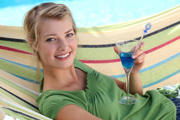 Woman in hammock drinking cocktail