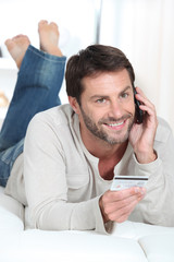 Smiling man using a credit card to pay for a purchase by phone