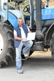 Famer with laptop computer stood by tractor