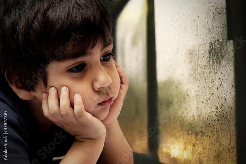 bambino che guarda la pioggia che cade dal vetro
