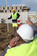 Two men measuring construction site