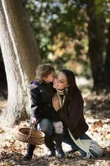 Little girl kissing her mum in woods