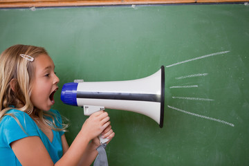 Young schoolgirl screaming through a megaphone