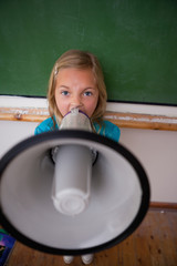Portrait of an angry schoolgirl yelling through a megaphone