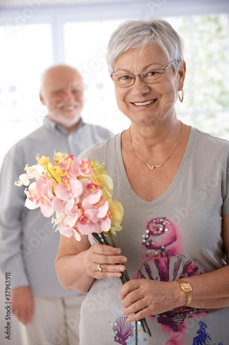Portrait of senior woman with bouquet smiling