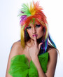 The beautiful young girl in a bright wig looking thoughtfully