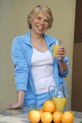 Mujer adulta bebiendo jugo de naranja.