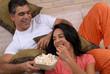 Pareja latina comiendo palomitas de maíz.
