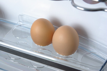 Fresh eggs on the fridge door shelf
