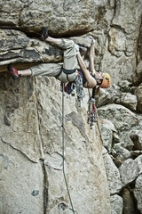 Rock climber clinging to a steep cliff.