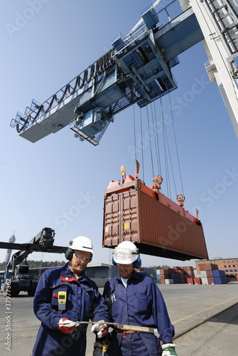 container port, trucks, cranes and workers
